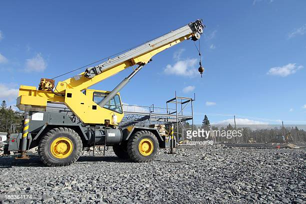 Yellow mobile construction crane driving over gray gravel