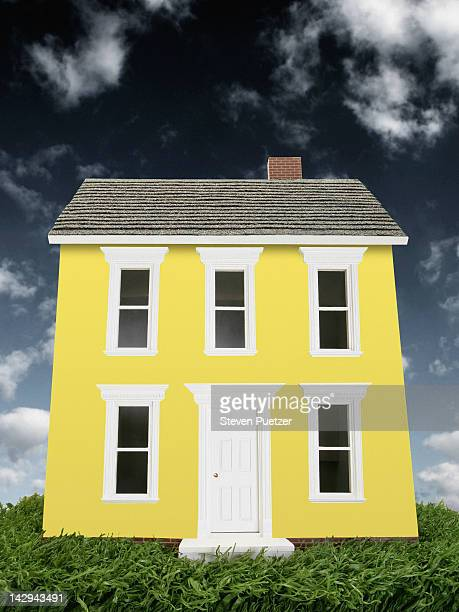 Yellow model house with stormy sky