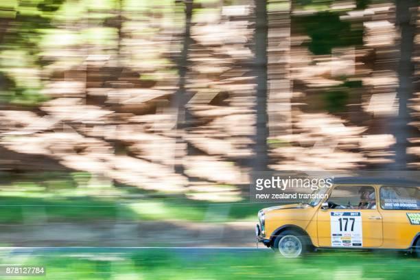1977 yellow Morris Mini panning motion with dark forest background, Targa NZ 2017