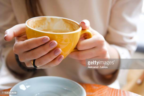 yellow mug in the hands of a young woman. girl holding a cup of coffee in a cafe. coffee break, breakfast. the concept of power. close up. - hot dirty girl stock photos and pictures