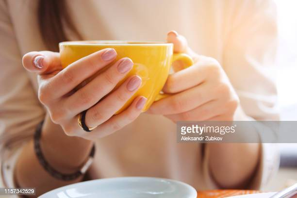 yellow mug in the hands of a young woman. girl holding a cup of coffee in a cafe. coffee break, breakfast. the concept of power. close up. - hot teen stock pictures, royalty-free photos & images