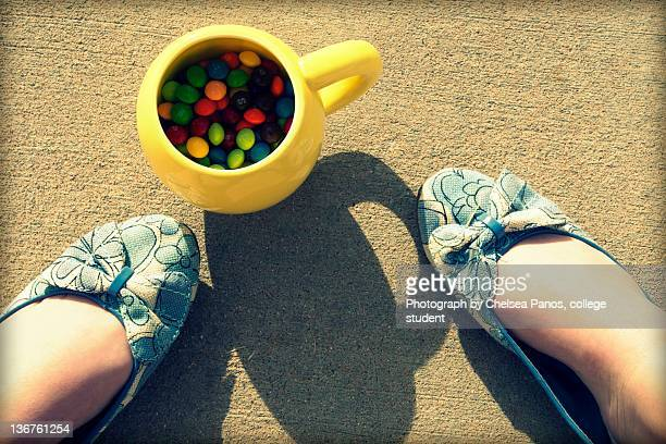 Yellow mug of skittles and blue shoes