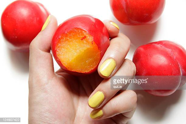 Yellow nail hand holding red plum