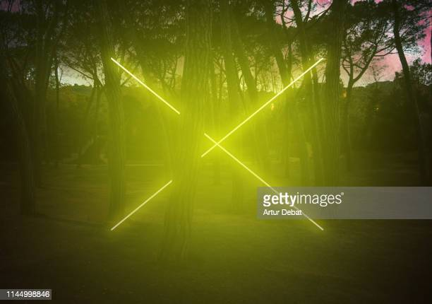 yellow neon with cross shape light between pine trees with futuristic visual effect. - x art fotografías e imágenes de stock