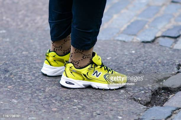 Yellow New Balance sneakers shoes and Gucci brown monogram socks are seen, during London Fashion Week Men's January 2020 on January 05, 2020 in...
