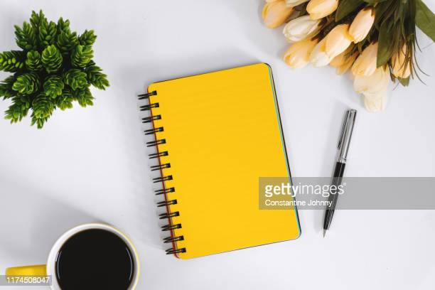 yellow notebook and coffee mug on work desk - 文房具 ストックフォトと画像