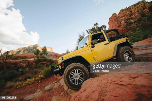 yellow off-road vehicle moving down on rocks at mountain against sky - jeep stock pictures, royalty-free photos & images