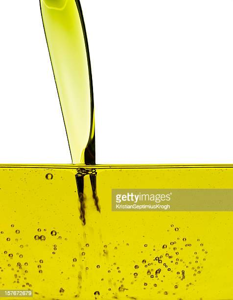 yellow oil being poured into a container - extra virgin olive oil stock pictures, royalty-free photos & images