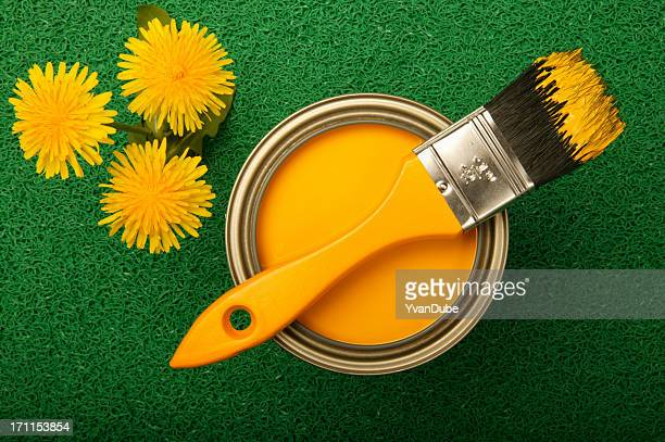 Yellow paint and dandelions on green turf