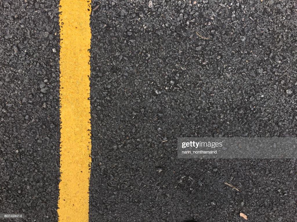 Yellow Paint Line On Black Asphalt Road Surface Texture