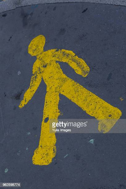 yellow painted walking man sign on asphalt - give way stock pictures, royalty-free photos & images
