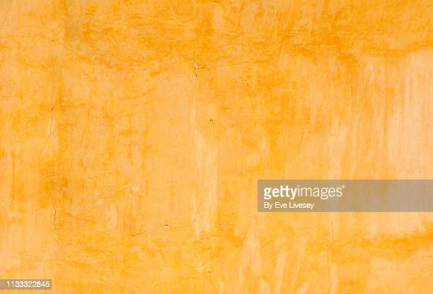 yellow painted wall texture - orange farbe stock-fotos und bilder