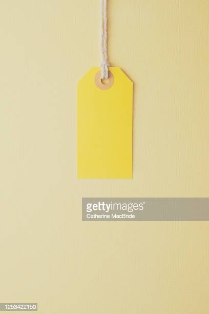 yellow paper label on a yellow background - catherine macbride fotografías e imágenes de stock