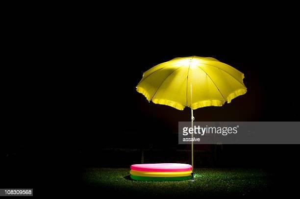 Gelben Sonnenschirm und Kinder-pool bei Nacht