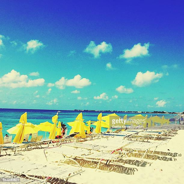 Yellow Parasols With Deck Chairs At Beach Against Sky