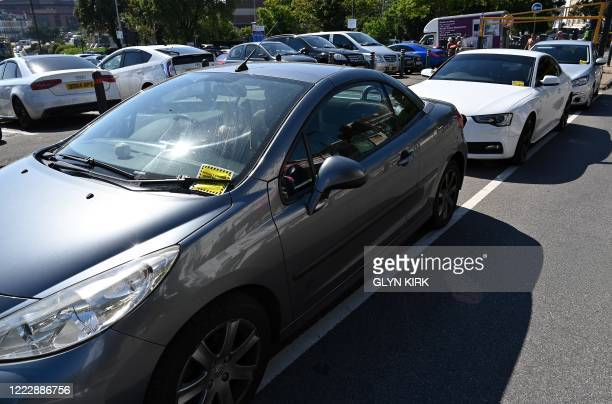 Yellow parking tickets are pictured on the windscreens of cars in a car park near the beach in Bournemouth, southern England, on June 25 as Britons...