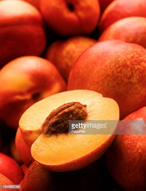 a yellow peach opened on top of other peaches - perzik stockfoto's en -beelden