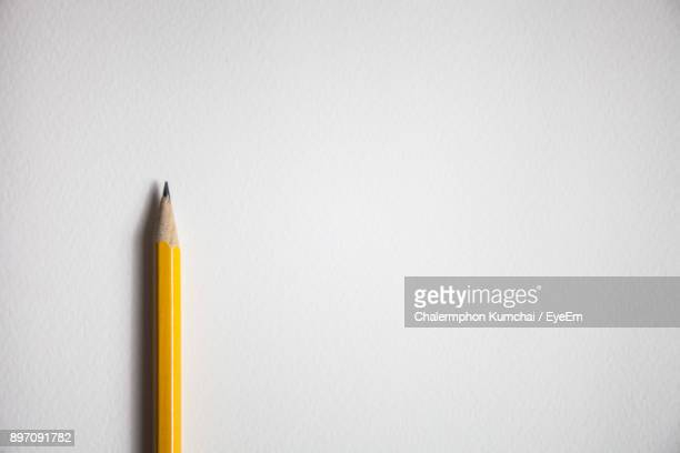 yellow pencil against white background - pencil stock pictures, royalty-free photos & images
