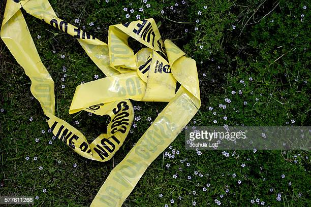 Yellow police crime scene tape rests in the grass on July 19 2016 in Baton Rouge Louisiana The crime scene tape lays in the area where three police...