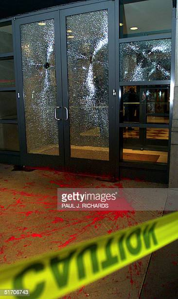 Yellow police crime scene tape surrounds cracked broken glass doors and red paint after protesters attacked the residential highrise building where...