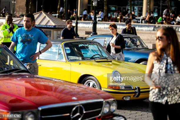 A yellow Porsche AG 911 center sits on display between a a red 1986 MercedesBenz AG 560SL luxury vehicle left and a blue 1961 Maserati SpA 3500GT...