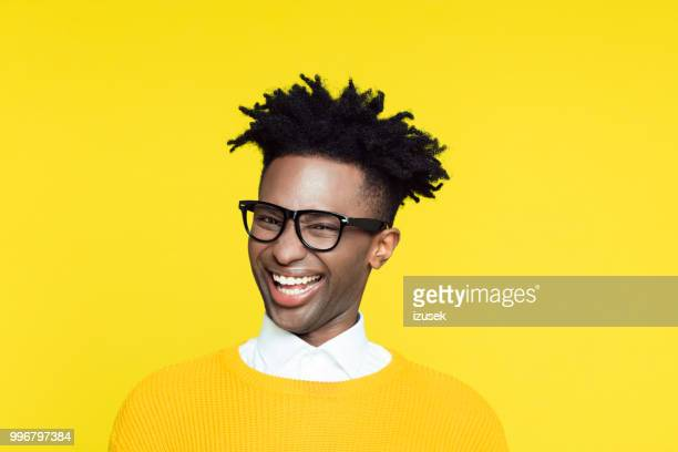 Yellow portrait of nerdy young man making funny face