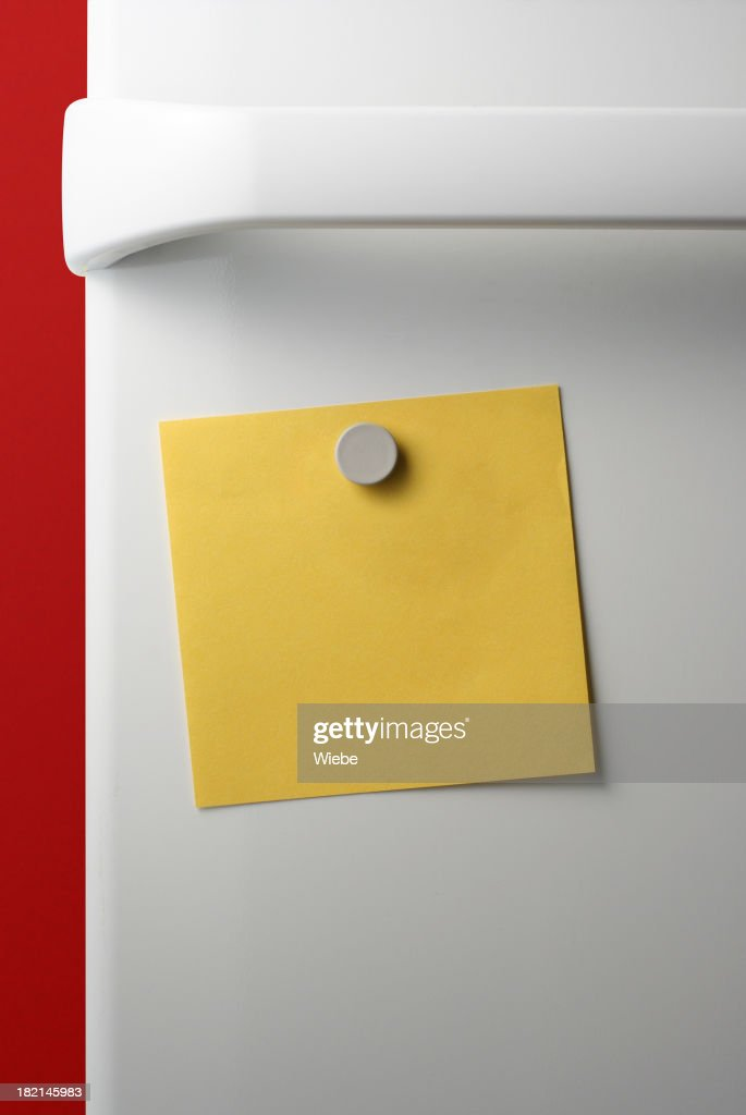 Yellow post it held on a fridge with one magnet : Stock Photo