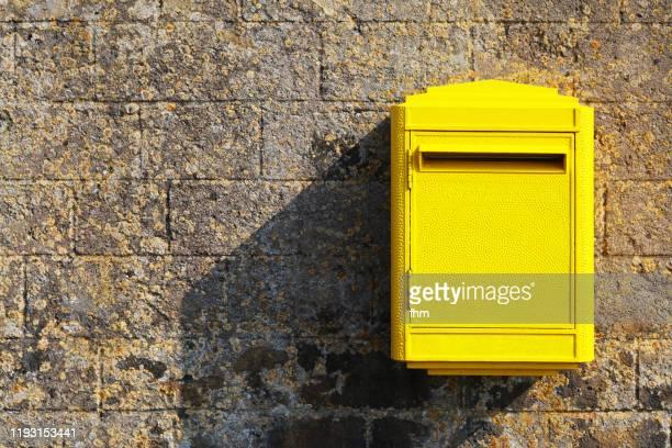 yellow postbox on a wall - carte france photos et images de collection