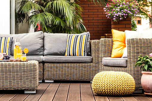 Yellow pouf on wooden terrace 947055810