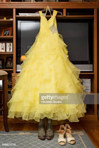 Yellow quinceanera dress hanging in living room