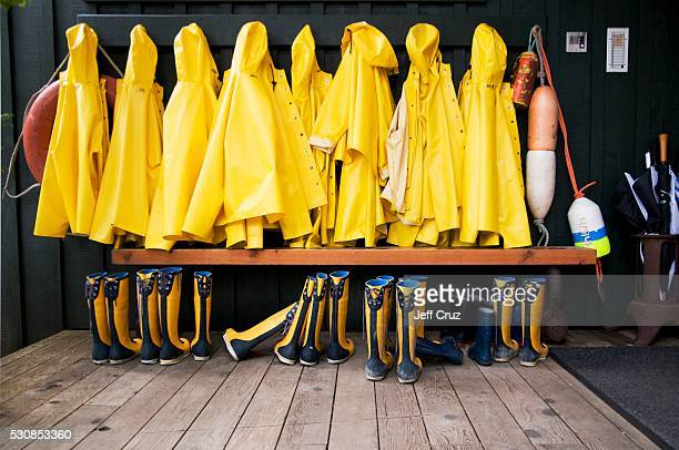 Yellow raincoats and rubber boots lined up, tofino, british columbia, canada