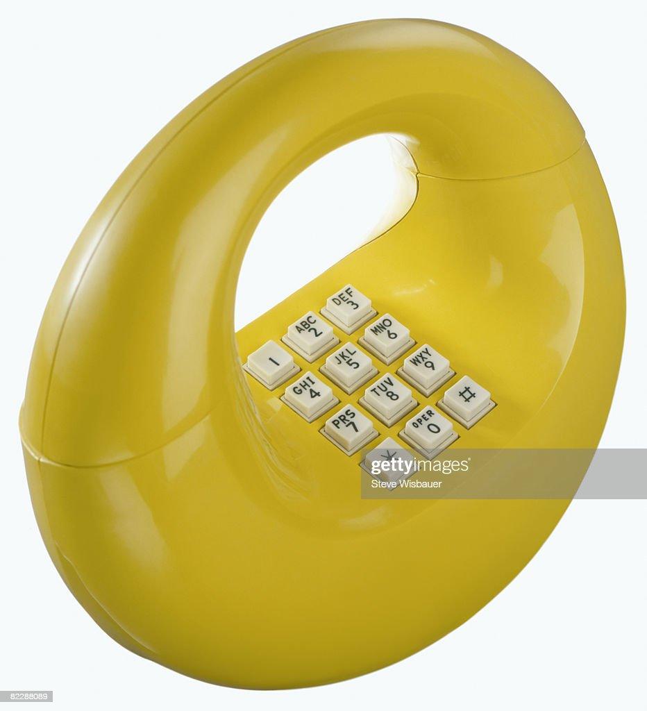 Yellow retro 1970s hoop donut or loop telephone : Stock Photo