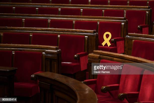 A yellow ribbon in memory of elected members of the parliament still in custody in jail in Madrid is seen on a seat of the Parliament of Catalonia on...