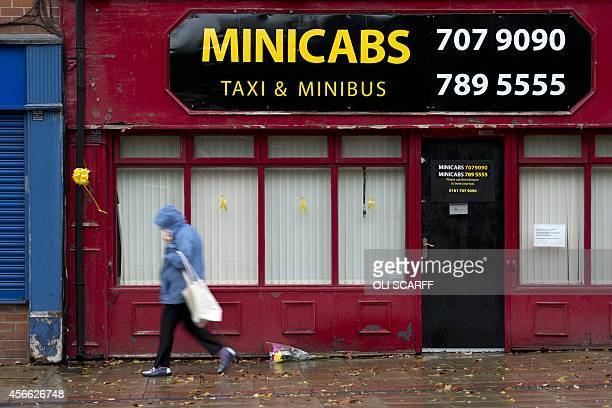 Yellow ribbons and a bouquet of flowers are seen as a woman walks past the minicab office where murdered aid worker Alan Henning worked in Eccles...