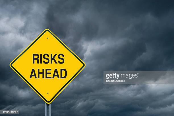 Yellow risks ahead caution sign in front of storm clouds