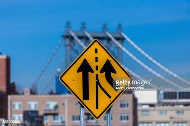 Yellow road sign with Manhattan Bridge in the background
