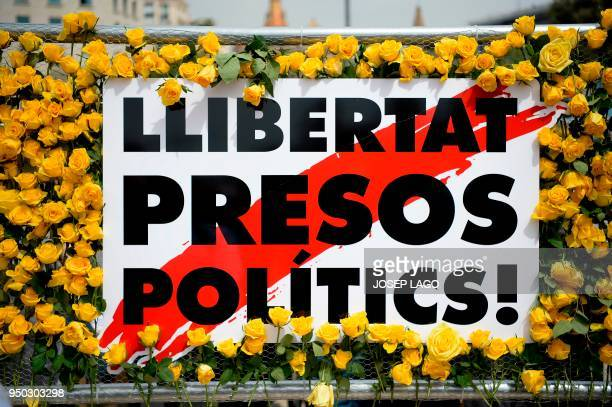 A yellow rose wall surrounds a banner reading 'Free political prisionners' during Sant Jordi festivities in Barcelona on April 23 on Saint George's...
