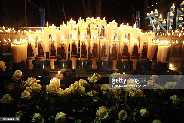 Yellow Roses By Burning Tea Light Candles At Night