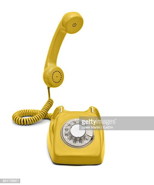 Yellow Rotary Phone Against White Background