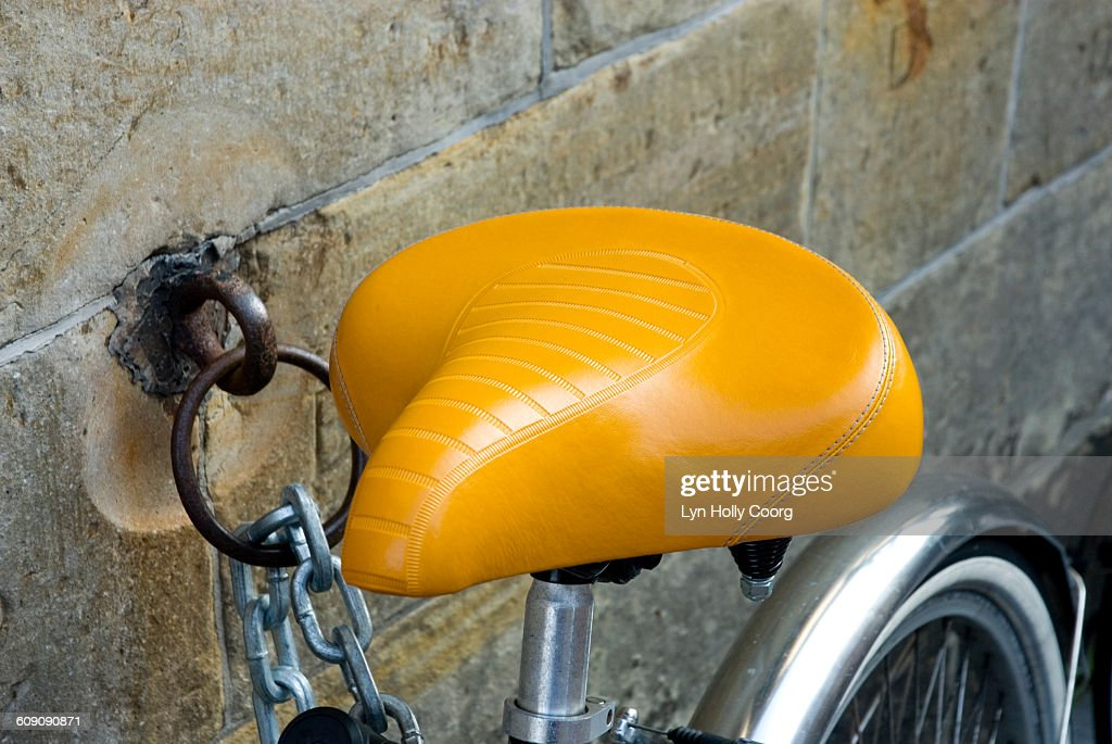 Yellow saddle of bike chained to wall : Stock Photo