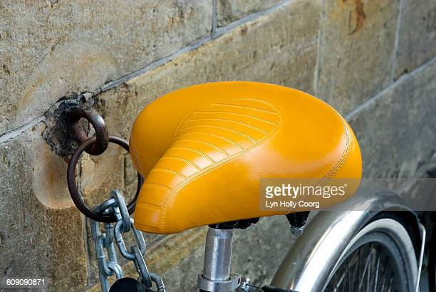 yellow saddle of bike chained to wall - lyn holly coorg photos et images de collection