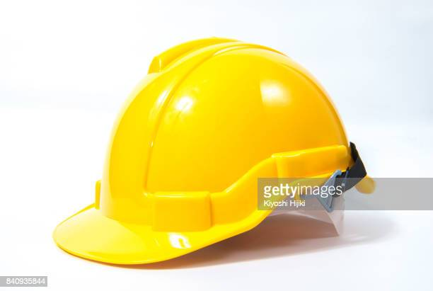 yellow safety helmet on white background - schutzhelm stock-fotos und bilder