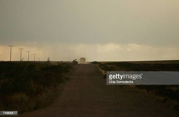 A yellow school bus carries a group of migrants through the vast desert landscape along the USMexico border before sunset June 29 2007 near Las...