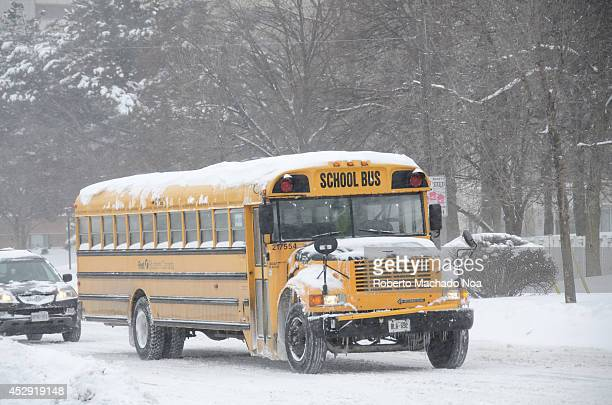 Yellow school bus or schoolbus during a snowing day harsh Winter due to the polar vortex or superstorm that hit Toronto during 2014