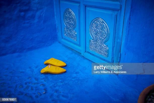 yellow shoes near ornate blue doorway, chefchaouen, chefchaouen, morocco - chefchaouen fotografías e imágenes de stock