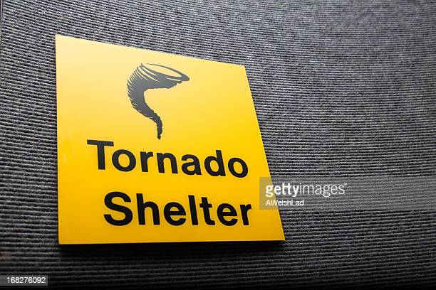 yellow sign got a tornado shelter on a wall - windbreak stock pictures, royalty-free photos & images