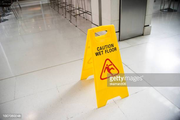 yellow sign wer floor on the ground - wet stock pictures, royalty-free photos & images