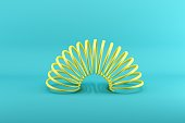 Yellow slinky isolated on blue background. Minimal conceptual idea concept.
