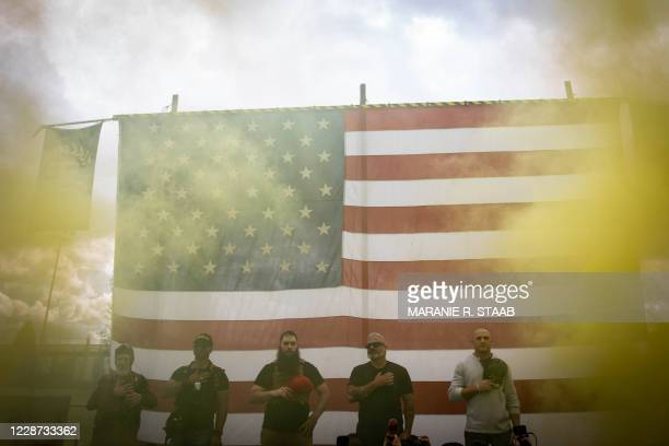 Yellow smoke fills the air as an American flag is raised at the start of a Proud Boys rally at Delta Park in Portland, Oregon on September 26, 2020....