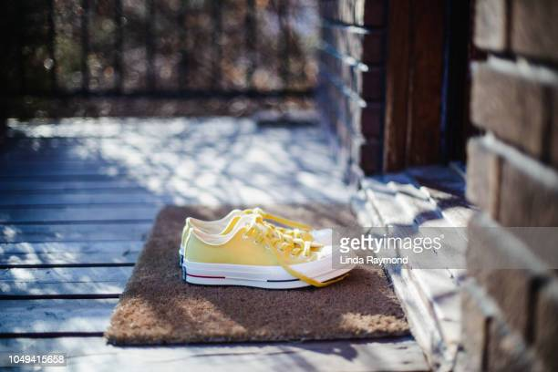 yellow sneckers on the porch - linda wilton stock pictures, royalty-free photos & images